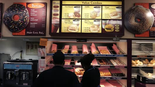 Workers stand in a Dunkin' Donuts.