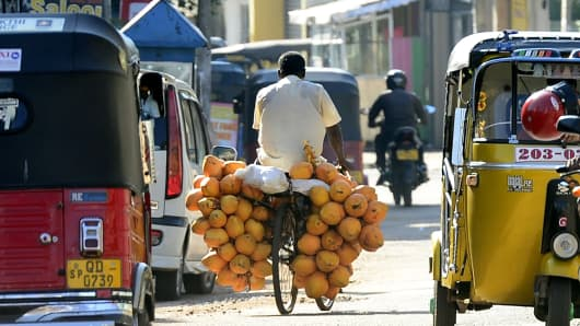 A Sri Lankan fruit vendor, selling king coconuts, rides his bicycle in Colombo on February 12, 2015.