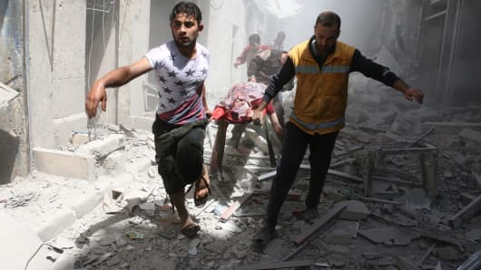 Syrian men carry a body on a stretcher amid the rubble of destroyed buildings following a reported air strike on the rebel-held neighbourhood of Al-Qatarji in the northern Syrian city of Aleppo, on April 29, 2016.