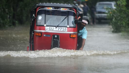 An auto-rickshaw drives along a flooded street in Colombo
