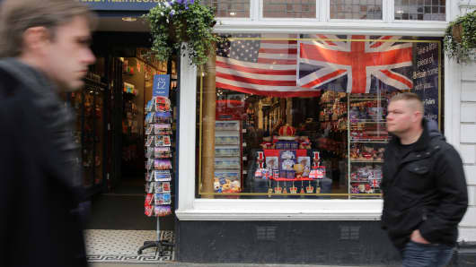 Pedestrians walk past a souvenir shop decorated with the US and British Union Flag before the visit by the US president Barack Obama and his wife US First Lady Michelle Obama to Windsor Castle in Windsor on April 22, 2016.