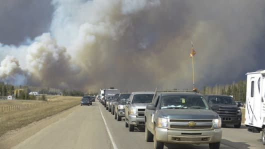 Smoke fills the air as people drive on a road in Fort McMurray, Alberta, Tuesday, May 3, 2016. At least half of a northern Alberta city was ordered evacuated Tuesday as a wildfire whipped by winds engulfed homes and sent ash raining down on residents.