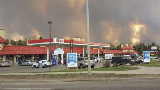 Smoke rises from a wildfire outside of Fort McMurray, Alberta, Tuesday, May 3, 2016. The entire population of the Canadian oil sands city of Fort McMurray, has been ordered to evacuate as a wildfire whipped by winds engulfed homes and sent ash raining down on residents.