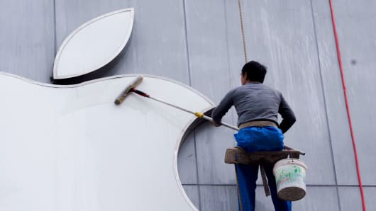 A worker cleaning an Apple logo in Suzhou, China.