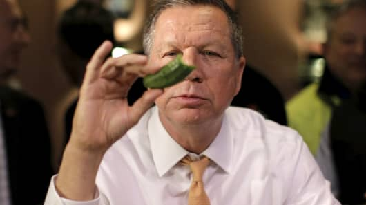 Republican U.S. presidential candidate John Kasich eats a pickle at PJ Bernstein's Deli Restaurant in New York City, April 16, 2016.