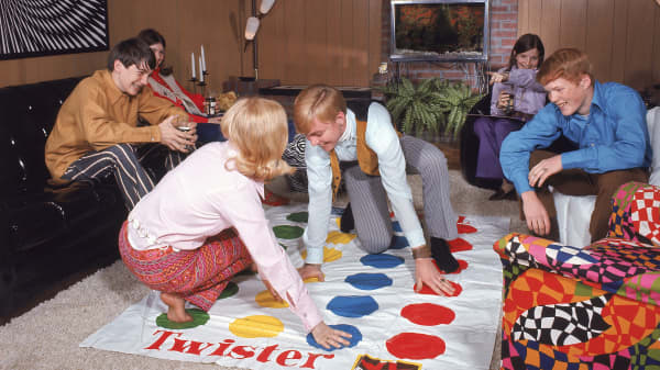 A boy and girl play the game Twister, as other young people watch in a paneled living room, circa 1968.