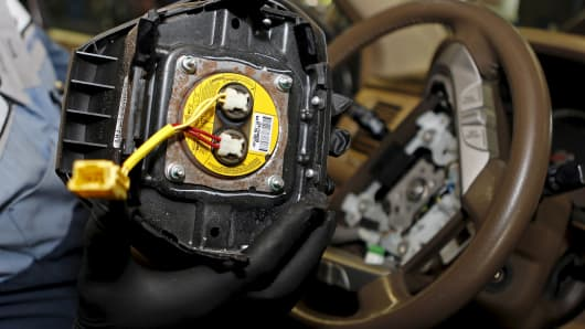 A technician holds a recalled Takata airbag inflator in Miami, Florida.
