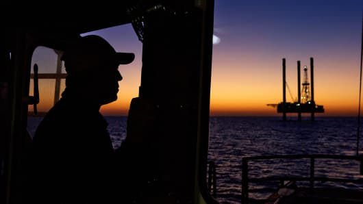 Silhouette of oil rig and worker