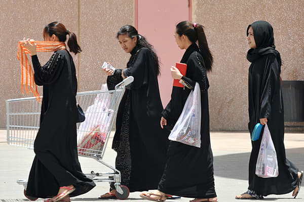 Filipina maids carry shopping bags out of a mall in Riyadh, Saudi Arabia. They are among the roughly 12 million workers from the Philippines employed outside the country.