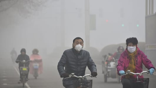 Citizens ride in the heavy smog on February 12, 2015 in Liaocheng, Shandong Province of China.