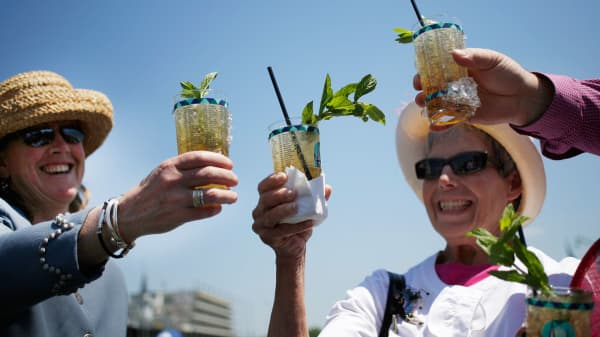 Racegoers who traveled to Churchill Downs from Colorado toast their Mint Julep bourbon cocktails while watching horse races on the eve of the Kentucky Derby in Louisville, Kentucky.