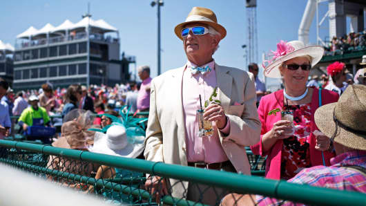 Racegoers sit in the stands at Churchill Downs while watching afternoon races on the eve of the Kentucky Derby in Louisville, Kentucky.
