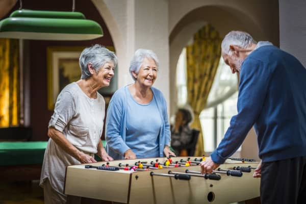Senior people playing foosball at nursing home