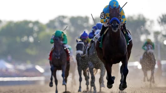 American Pharoah #5, ridden by Victor Espinoza, crosses the finish line ahead of Frosted #6, ridden by Joel Rosario, and Keen Ice #7, ridden by Kent Desormeaux, to win the 147th running of the Belmont Stakes at Belmont Park on June 6, 2015 in Elmont, New Y