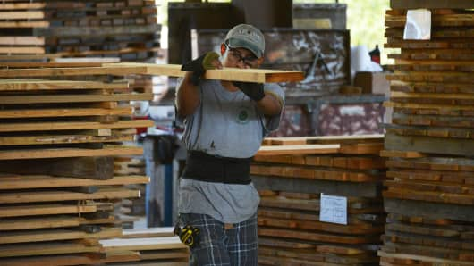 A worker carries a Heart Pine plank of lumber in the sawmill at the Goodwin Co. facility in Micanopy, Florida,