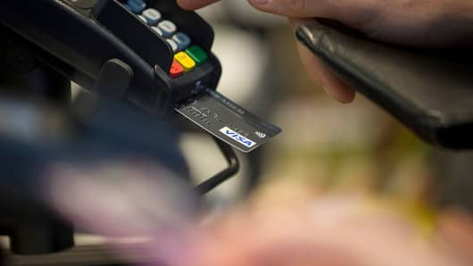 A customer enters their pin number while making a chip and pin payment using a Visa payment card.