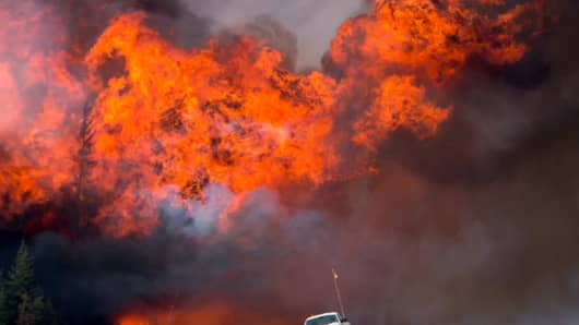 A wildfire burns behind an abandoned truck on Alberta Highway 63 near Fort McMurray, Alberta, Canada, on Saturday, May 7, 2016