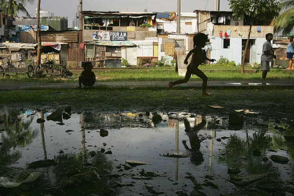 A Filipino boy runs near puddles along the railroad tracks in Pasay City in Manila in July 2005. The area is now being gentrified but slums remain.