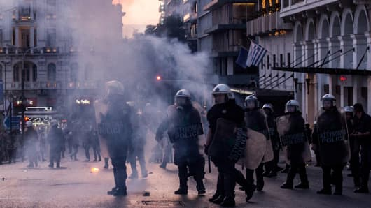Riot policemen are seen through smoke, after minor scale clashes during a protest in Athens on May 8, 2016.