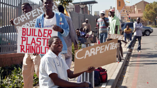 Johannesburg, South Africa: Laborers needing work hold signs with their specialities outside a hardware store in Fourways.