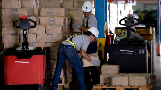 Workers load packages of corn flour at a distribution center of food company 'Empresas Polar' in Maracay, Venezuela.