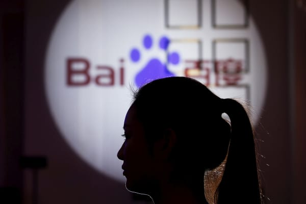A woman is silhouetted against the Baidu logo in Shanghai.