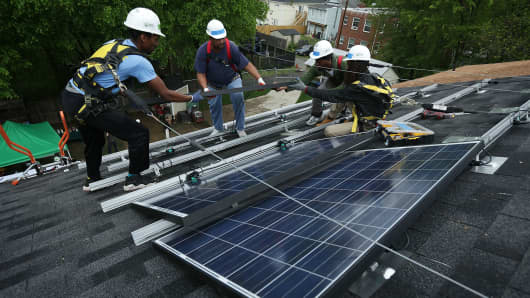 Workers put solar panels down during an installation May 3, 2106 in Washington, DC. The installation marked the one millionth in the U.S. in the past 40 years.