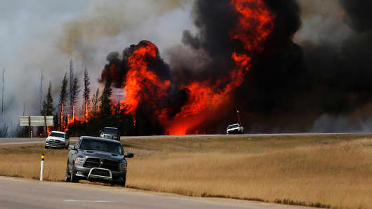 Smoke and flames from the wildfires erupt behind cars on the highway near Fort McMurray, Alberta, Canada, May 7, 2016.