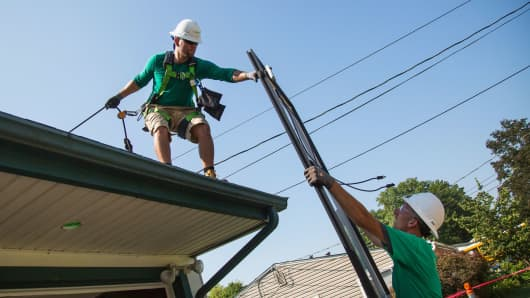 SolarCity employees prepare to install solar panels on the roof of a home in Kendall Park, New Jersey.
