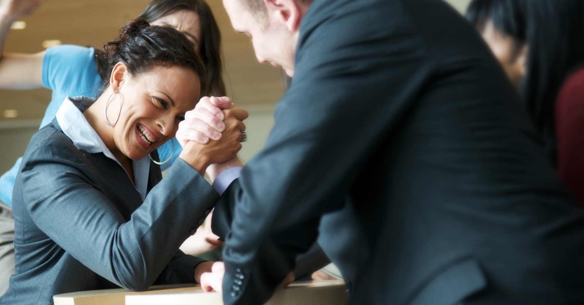Business professionals arm wrestling in the office