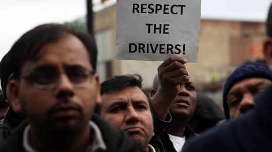 Uber drivers protest the company's recent fare cuts and go on strike in front of the car service's New York offices on February 1, 2016.