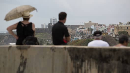Tourists take a break after visiting the El Morro fort, where part of Old San Juan, Puerto Rico, is visible.