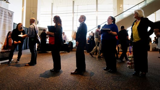 Job seekers wait to talk to a recruiter at a health care job fair sponsored by the Colorado Hospital Association in Denver.
