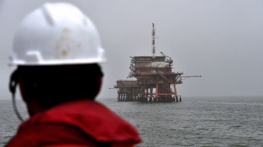 Oil Worker looking out to a rig