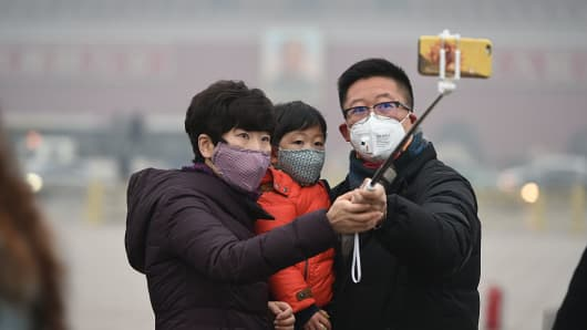 Tourists wearing masks take a selfie at Tian'anmen Square in the heavy smog on December 9, 2015 in Beijing, China.