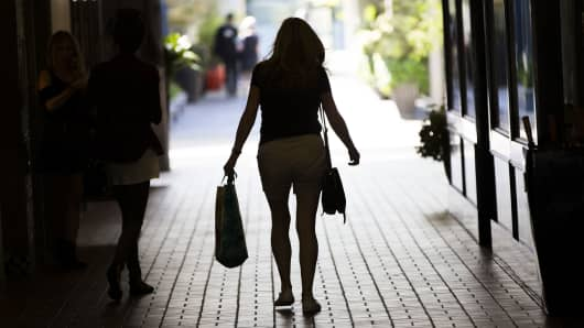 The silhouette of a shopper is seen as she walks through the University Village open air shopping center in Seattle, Washington.
