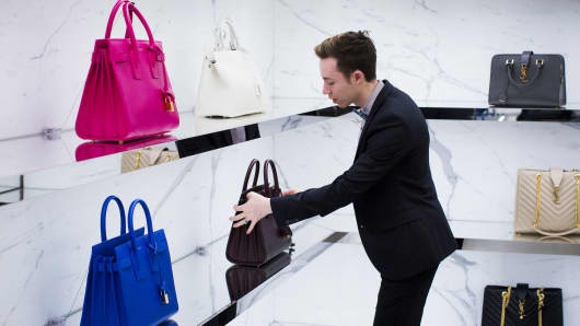 A retail worker adjusts a display of handbags in a Nordstrom store.