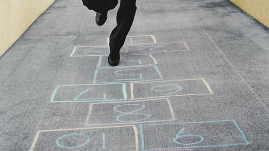 Businessman playing hopscotch, trades