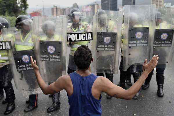 A protester gestures in front of police during an opposition march in Caracas, Venezuela, on Wednesday, May 11, 2016.