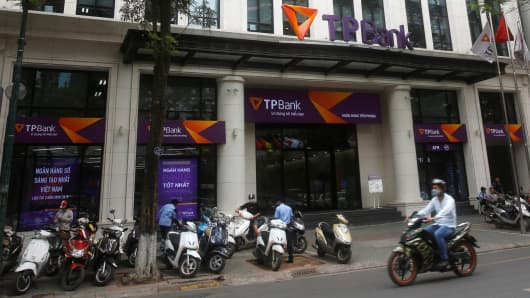A man rides a motorcycle past the Vietnamese commercial Tien Phong bank in Hanoi May 13, 2016.