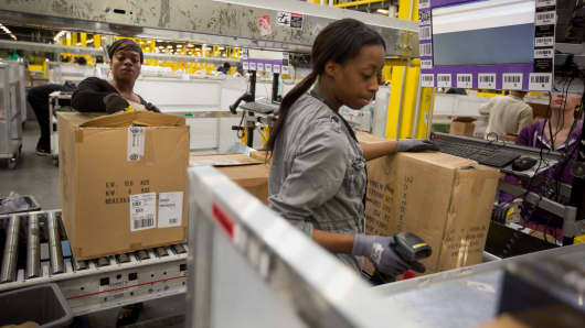 Amazon.com employees unpack boxes inside a fulfillment center in Robbinsville, New Jersey.