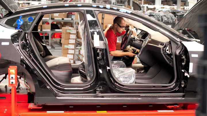 An employee works on a Telsa Motors Model S sedan as it makes its way along an assembly line at company's assembly plant in Fremont, California.