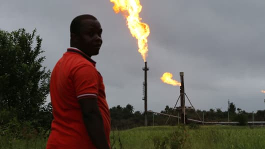 A man looks on as flares burn from pipes at an oil flow station in Idu, Rivers State, Nigeria.