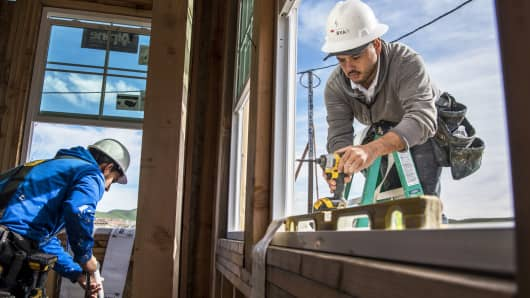 Contractors install a window on a home under construction at the Toll Brothers housing development in San Ramon, California.