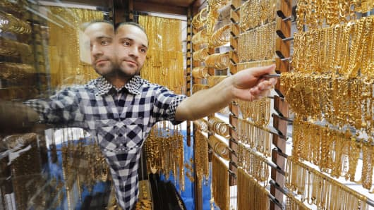 A Jordanian goldsmith places gold chains for display at his jewelry shop in Amman, Jordan.