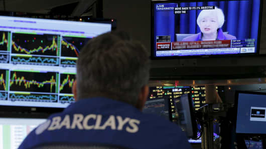 Traders work on the floor of the New York Stock Exchange (NYSE) as a television screen displays coverage of U.S. Federal Reserve Chairmman Janet Yellen shortly after the announcement that the U.S. Federal Reserve had hiked interest rates for the first time