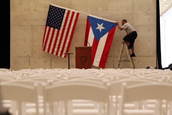 A worker takes off U.S and Puerto Rican flag after rally of U.S. Democratic presidential candidate Bernie Sanders in San Juan, Puerto Rico, May 16, 2016.