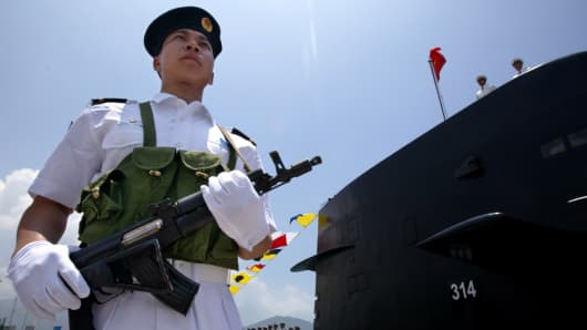 A Chinese Naval officer stands guard beside a submarine at the Ngong Shuen Chau Naval Base in Hong Kong.
