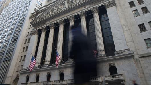 Man walks by NYSE exterior, gloom, dark figure silhouette