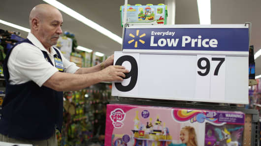 A Walmart employee changes a price at a store in Miami.